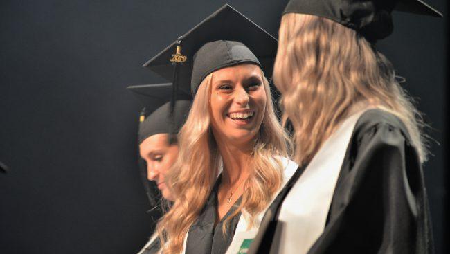 Deux jeunes diplômés se regardent en souriants sur la scène.