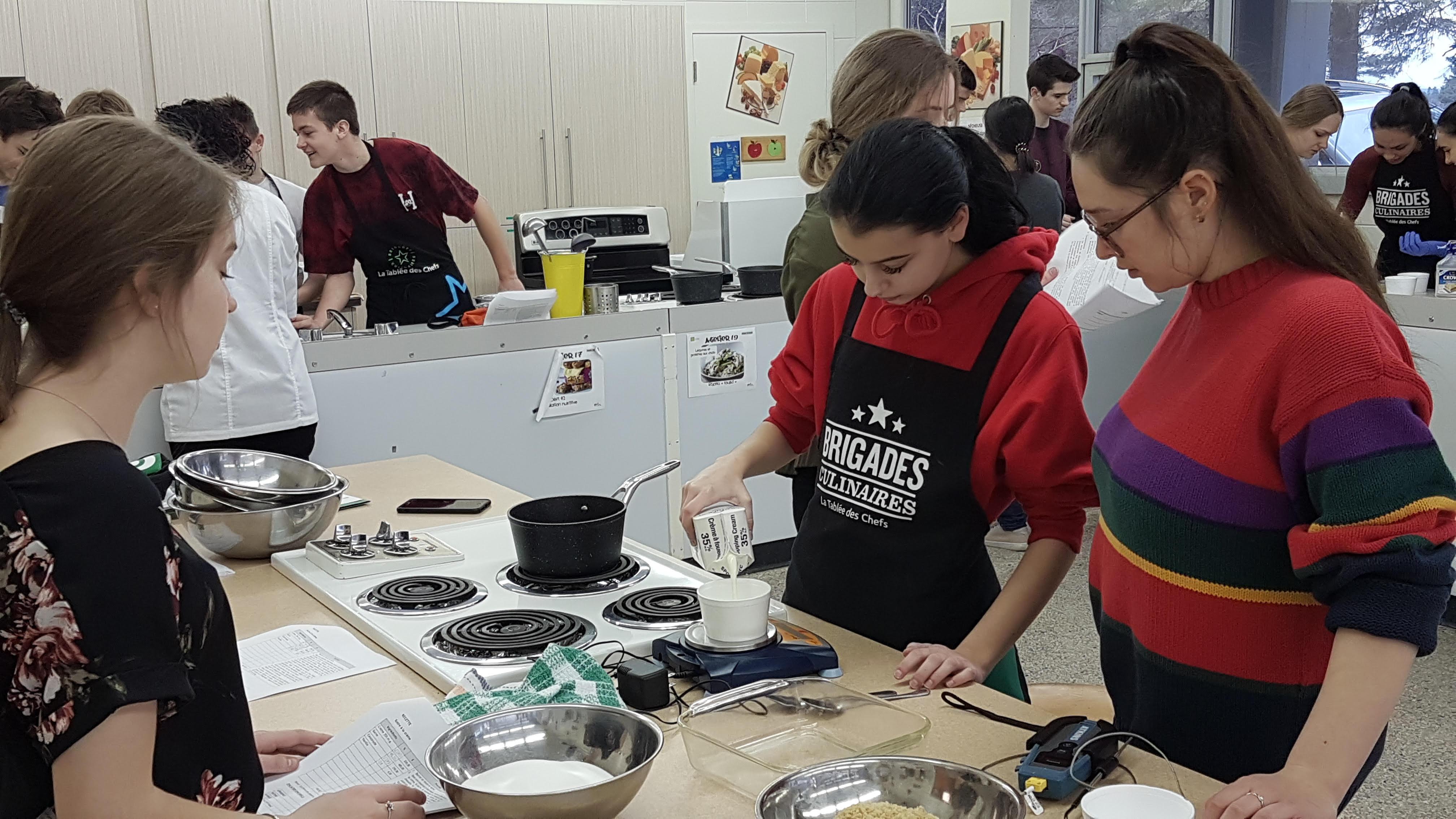 Trois étudiantes du secondaire de Charles-Gravel concentrées sur leur préparation. L'une d'elle verse du lait dans une casserole.