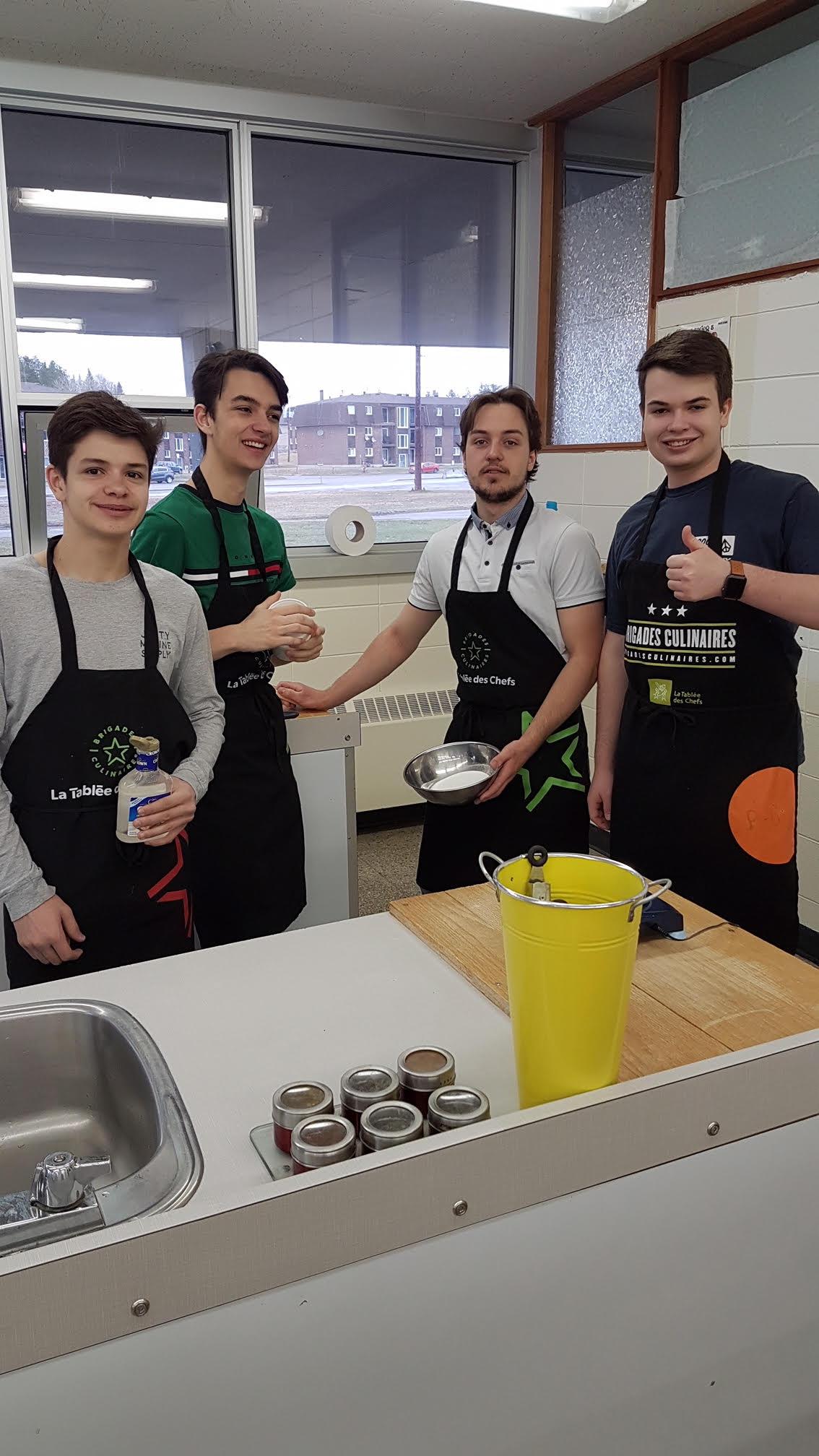 Quatre étudiants du secondaire de Charles-Gravel, posant avec des ustensiles de cuisine.