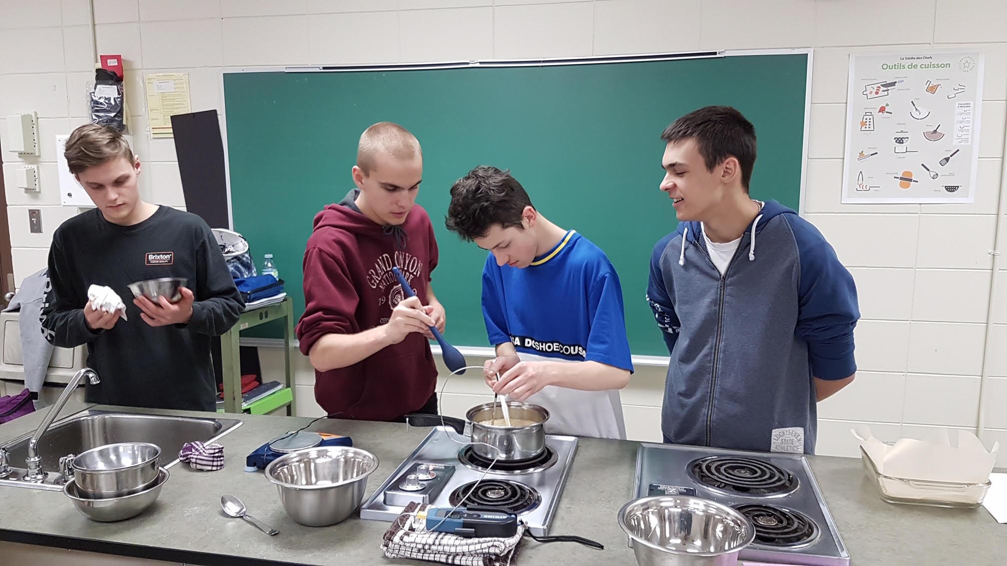 Quatre étudiants concentrés sur leur préparation au dessus de la casserole et un nettoie un récipient.
