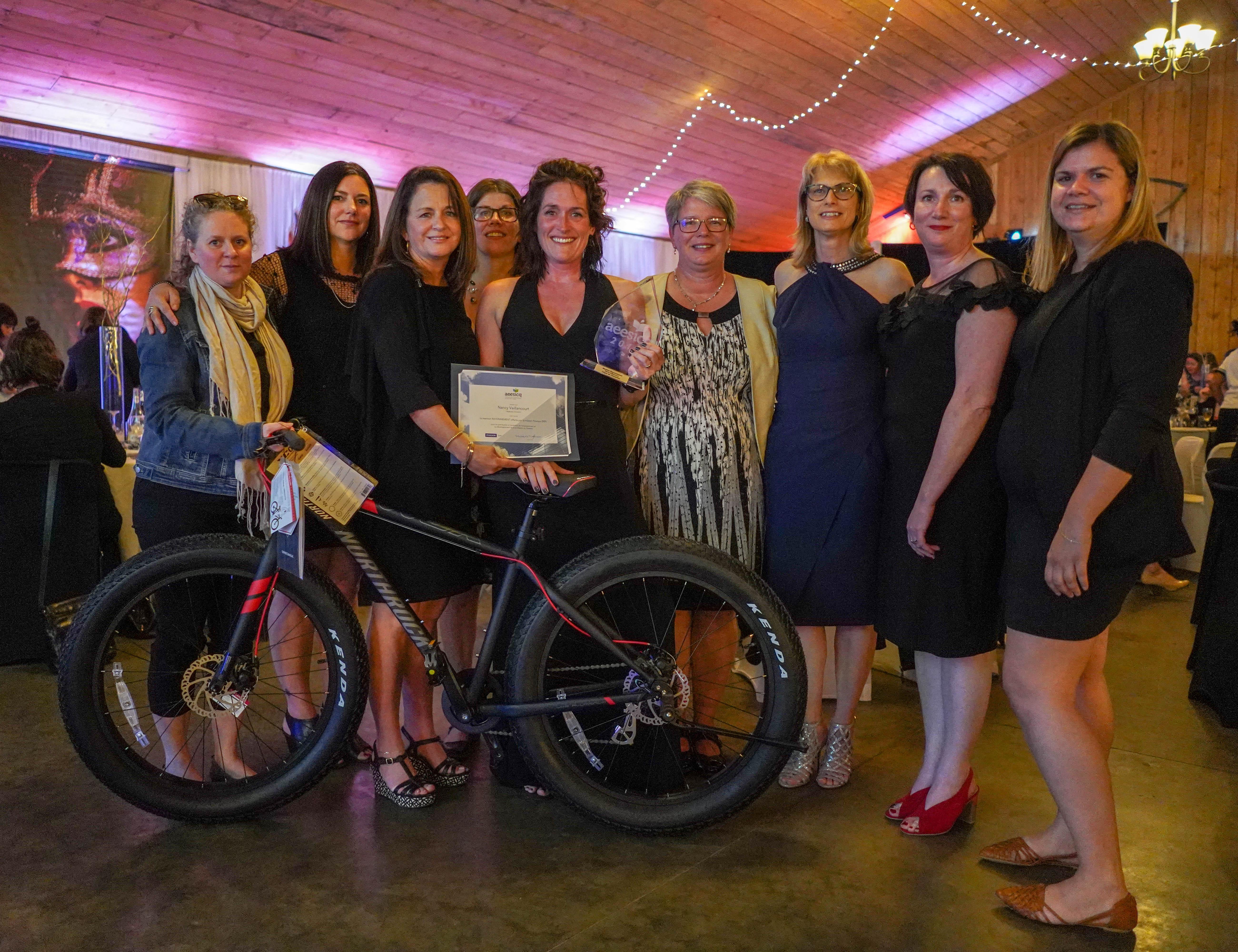 Photo portrait de neuf femmes représentants l'Association des enseignantes et enseignants en soins infirmiers des collèges du Québec, ainsi que la collaboration de Pearson ERPI. Au milieu se trouve la gagnante Nancy Vaillancourt avec ses prix et un vélo.
